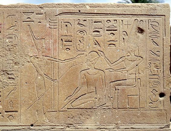 Hatshepsut, de rodillas, recibiendo la bendición de Amón (en una silla a la derecha) y Mut (de pie a la izquierda)